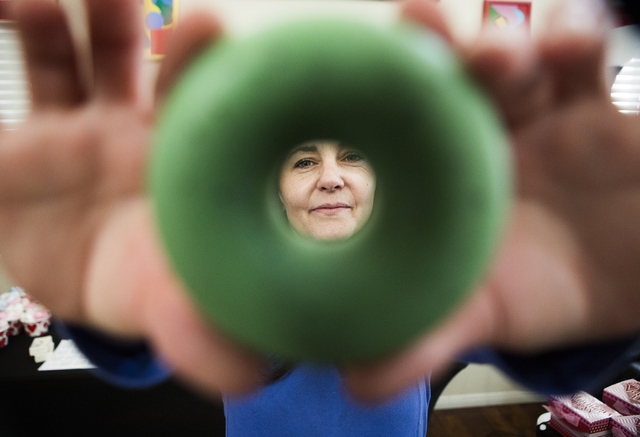 Carmen Iclodean, owner of Earth's Raw Beauty, is framed between a bar of handmade soap shaped like a donut on Monday, Jan. 23, 2017. (Jeff Scheid/Las Vegas Review-Journal)@jeffscheid
