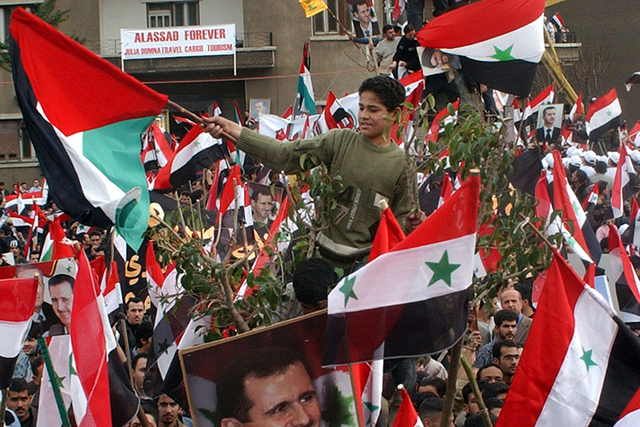 In a 2005 file photo, supporters march in Mezzah, an upscale Damascus neighborhood where President Bashar Assad lives. Syria accused Israel of firing rockets that struck near Mezzah early on Frida ...