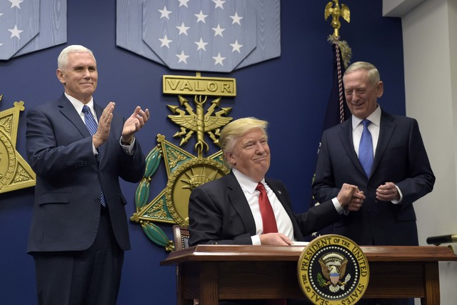 President Donald Trump grabs the hand of Defense Secretary James Mattis, after he signed an executive action on rebuilding the military during an event at the Pentagon in Washington, Friday, Jan.  ...