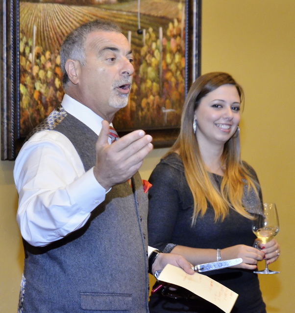 """Gino Ferraro, principal with Ferraro's Italian Restaurant and Wine Bar, left, talks with diners as Letizia Patane, export manager for Passopisciaro wines, listens during the """"Taste and Lear ..."""