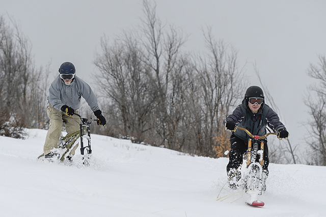 Playing in the snow, Mike Kerr, left, and Taylor Hobson ski bike off the top of Emigration Canyon in Utah, Wednesday, Jan. 4, 2016. Wet winter weather slammed much of the West on Wednesday. (Franc ...
