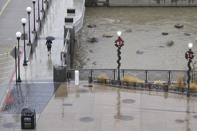 A woman walks in the rain in downtown Reno on Wednesday, Jan. 4, 2017, across a bridge above the rising waters of the Truckee River. A flashflood was in effect in Reno, 40 miles downstream from La ...