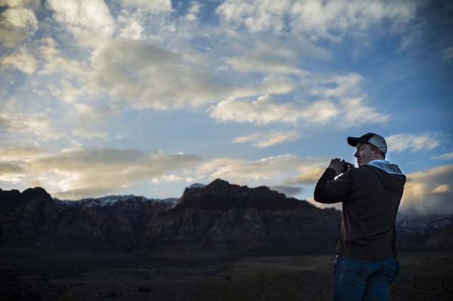 CJ Parker of Texas takes a photo as the sun sets at the Red Rock Canyon National Conservation Area overlook outside of Las Vegas on Friday, Jan. 13, 2017. (Chase Stevens/Las Vegas Review-Journal)  ...