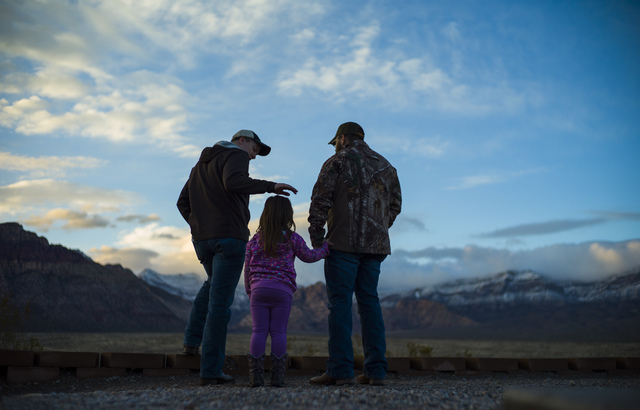 William Parker, right, with daughter Amelia, 4, both of Las Vegas, take in the sunset with CJ Parker of Texas from the Red Rock Canyon National Conservation Area overlook outside of Las Vegas on F ...