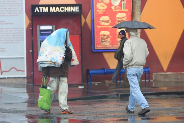 Pedestrians shield themselves from rain in Las Vegas on Friday, Jan. 13, 2017. (Brett Le Blanc/Las Vegas Review-Journal) @bleblancphoto