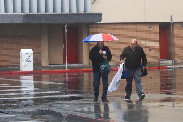 Pedestrians cross the street in the rain in Las Vegas on Friday, Jan. 13, 2017. (Brett Le Blanc/Las Vegas Review-Journal) @bleblancphoto