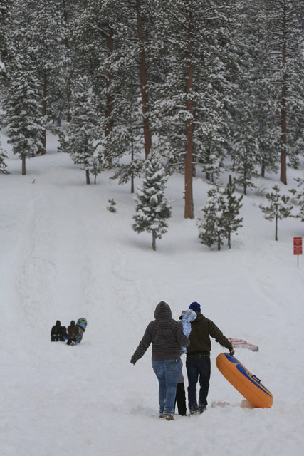 A family starts the trek up a hillside to enjoy tubing during a snow day in Lee Canyon outside of Las Vegas on Friday, Jan. 13, 2017. Mount Charleston has seen more than a foot of snowfall in the  ...