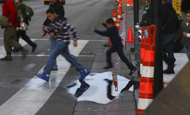 Children jump over a puddle along Fremont Street at Las Vegas Boulevard in downtown on Friday, Jan. 13, 2017. (Chase Stevens/Las Vegas Review-Journal) @csstevensphoto