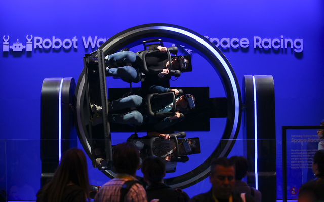 Attendees use virtual reality headsets while on a motion-controlled ride at the Samsung booth during CES at the Las Vegas Convention Center in Las Vegas on Friday, Jan. 6, 2017. (Chase Stevens/Las ...