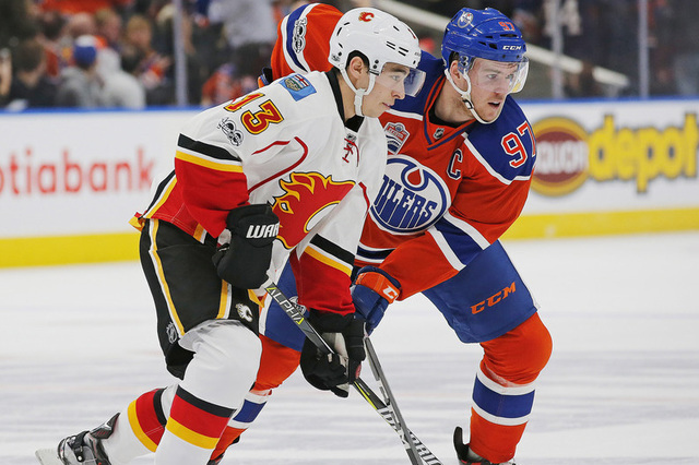 Jan 14, 2017; Edmonton, Alberta, CAN; Calgary Flames forward Johnny Gaudreau (13) and Edmonton Oilers forward Connor McDavid (97) battle for a loose puck during the first period at Rogers Place. M ...