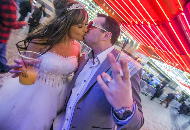 Newlyweds Rachel and Thomas Gledhill  from United Kingdom share a kiss during America's Party on Fremont Street on Saturday, Dec. 31, 2016. Jeff Scheid/Las Vegas Review-Journal Follow @jeffscheid