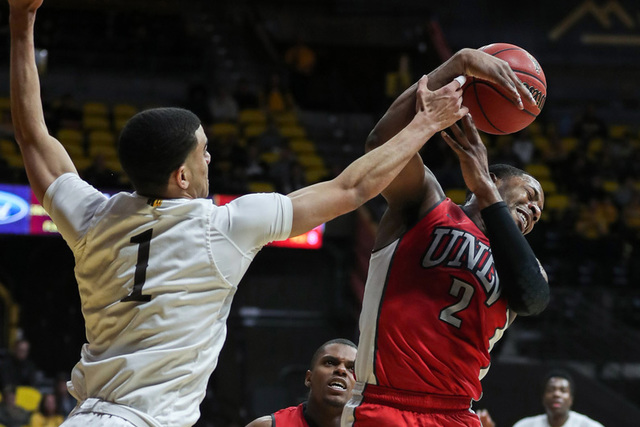 UNLV Rebels guard Uche Ofoegbu (2) grabs a rebound against Wyoming Cowboys guard Justin James (1) during the second half at Arena-Auditorium. The Cowboys beat the Rebels 66-65. (Troy Babbitt/USA T ...