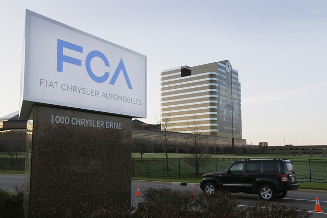 In this Tuesday, May 6, 2014, file photo, a vehicle moves past a sign outside Fiat Chrysler Automobiles world headquarters in Auburn Hills, Mich.    (AP Photo/Carlos Osorio, File)