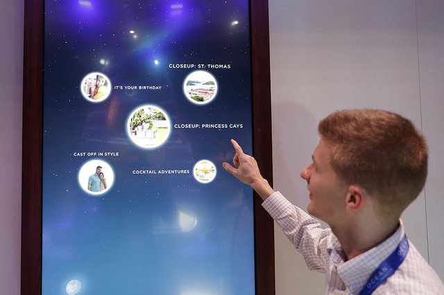 Miles Clark of Carnival Corp. demonstrates the Ocean Compass interface before CES International, Tuesday, Jan. 3, 2017, in Las Vegas. The linchpin of the concierge technology is a medallion the si ...