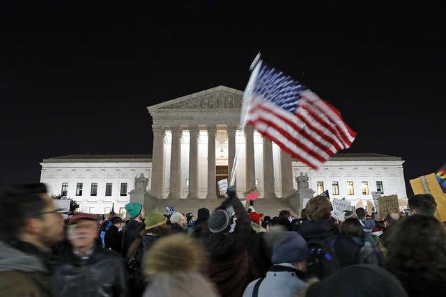 A protester waves an American flag in front of the Supreme Court during a protest about President Donald Trump's recent executive orders, Monday, Jan. 30, 2017 in Washington. (AP Photo/Alex Brandon)