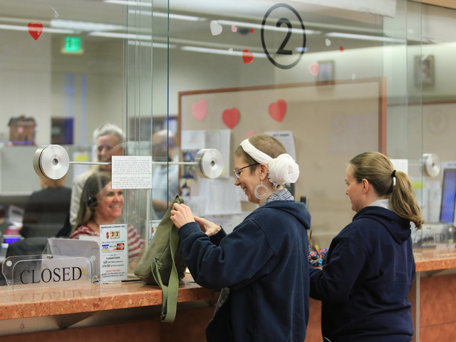 Jennifer Dickerson, 37, left, and Amanda Falzone, 34, center, are issued the 10,000th same sex marriage license in Clark County by Karen Stuart, 43, at the Clark County Marriage License Bureau in  ...