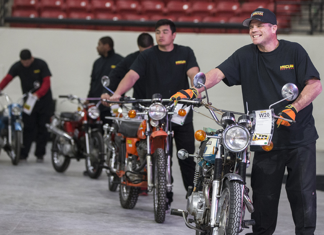 Dennis Archer, right, walks the next bike to auctioned on to the stage during the 26th annual Mecum Las Vegas Motorcycle Auction at South Point hotel-casino, in Las Vegas. Over 1,000 antique, vint ...