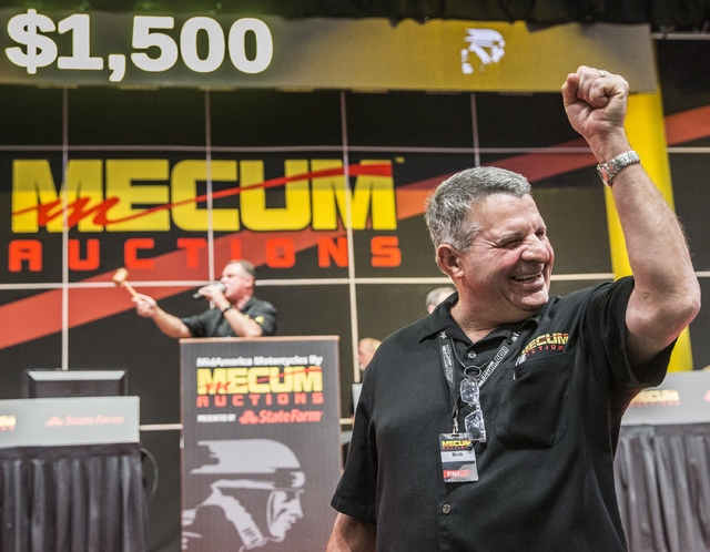 Auctioneer Bob McGlothlen, right, celebrates a winning bid during the 26th annual Mecum Las Vegas Motorcycle Auction at South Point hotel-casino, in Las Vegas. Over 1,000 antique, vintage and coll ...
