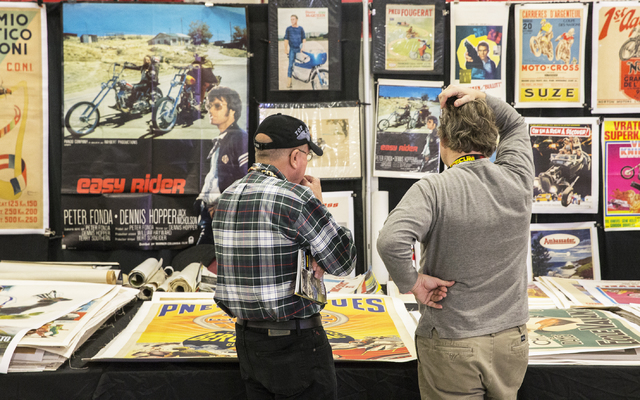 Kurt Carlson, left, shops for antique posters with Damien Delabre during the 26th annual Mecum Las Vegas Motorcycle Auction at South Point hotel-casino, in Las Vegas. Over 1,000 antique, vintage a ...