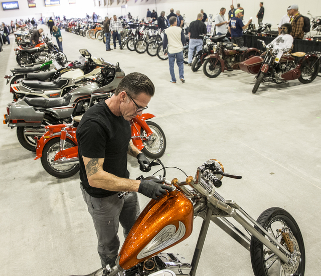 Troy Lepird, left, from Phoenix, Arizona, polishes his custom bike from Envy Cycle Creations during the 26th annual Mecum Las Vegas Motorcycle Auction at South Point hotel-casino, in Las Vegas. Ov ...