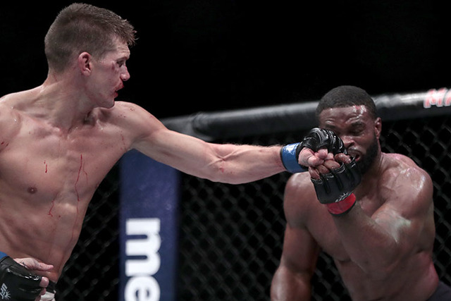 Stephen Thompson, left, connects with Tyron Woodley during a welterweight title mixed martial arts bout at UFC 205, early Sunday, Nov. 13, 2016, at Madison Square Garden in New York. (AP Photo/Jul ...