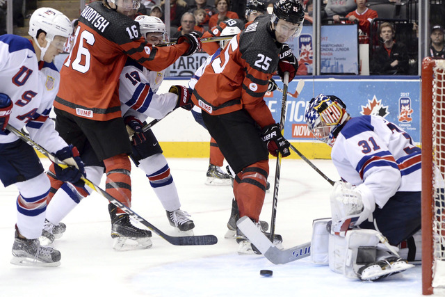United States goaltender Joseph Woll (31) makes a save on Canada forward Nicolas Roy (25) during during the third period of a world junior championship hockey game in Toronto on Saturday, Dec. 31, ...