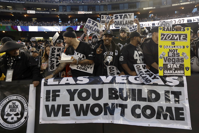 In this Nov. 6, 2016, file photo, Oakland Raiders fans hold up signs about the team's possible move to Las Vegas during an NFL football game between the Raiders and the Denver Broncos in Oakland,  ...