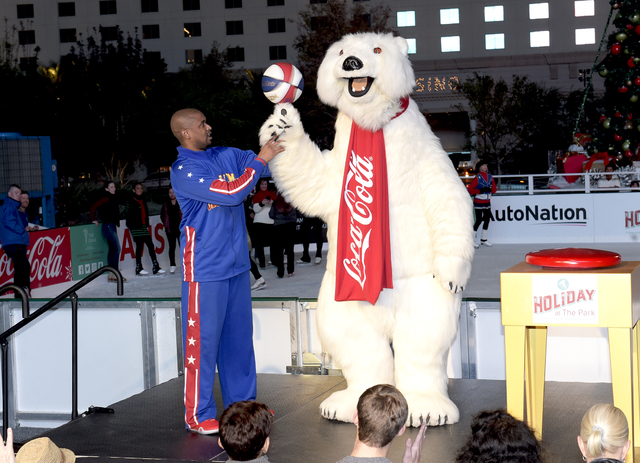 Harlem Globetrotter Scooter Christensen of Las Vegas teaches the Coca-Cola Bear to spin a basketball on his paw during The Park's first-ever tree-lighting ceremony Monday, Nov. 21, 2016, in Las  ...