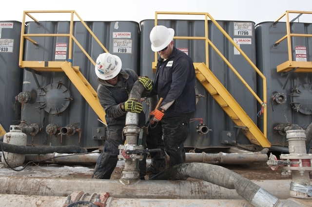 Mody Torres, left, and Josh Anderson of Select Energy Services connect hoses between a pipeline and water tanks at a Hess fracking site near Williston, North Dakota, Nov. 12, 2014. (Andrew Cullen/ ...