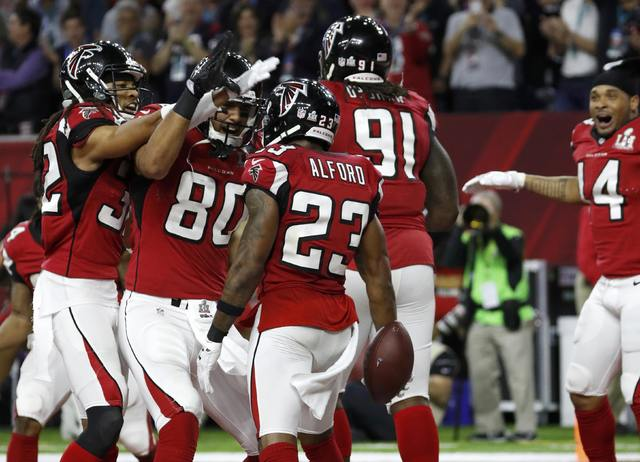 Atlanta Falcons' Robert Alford (23) celebrates his 82-yard touchdown run with teammates after making an interception on New England Patriots' quarterback Tom Brady (not pictured) during the second ...