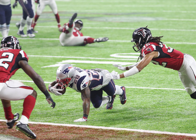 Feb 5, 2017; Houston, TX, USA; New England Patriots running back James White (28) sores a touchdown between Atlanta Falcons strong safety Keanu Neal (22) and Jalen Collins (32) in the third quarte ...