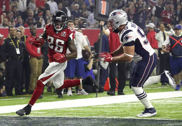 Atlanta Falcons' Tevin Coleman (L) runs into the end zone to score past New England Patriots' Rob Ninkovich during the third quarter of Super Bowl LI in Houston, Texas, U.S., February 5, 2017. REU ...