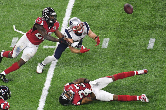 New England Patriots wide receiver Julian Edelman (11) and Atlanta Falcons strong safety Keanu Neal (22) dive to catch a tipped pass in the fourth quarter during Super Bowl LI at NRG Stadium. (Ric ...