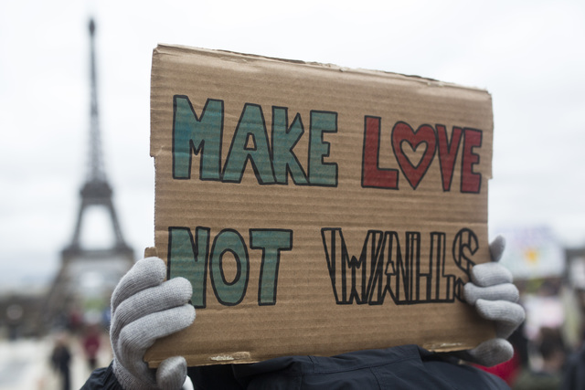 """A woman holds a banner reading """" Make love not walls"""" during a gathering to protest U.S. President Donald Trump's recent travel ban to the U.S. at Trocadero Plaza next to the Eiffel Tower in Paris ..."""