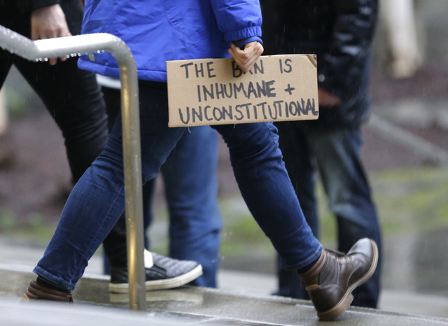 """A person walks away from the federal courthouse in Seattle carrying a sign that reads """"The Ban is Inhumane and Unconstitutional,"""" Friday, Feb. 3, 2017, following a hearing in federal court in Seat ..."""