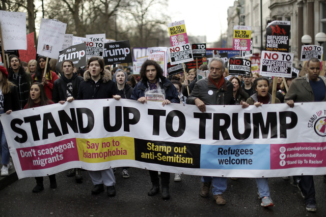 People hold a banner as they take part in a protest march in London, against U.S. President Donald Trump's ban on travelers and immigrants from seven predominantly Muslim countries entering the U. ...