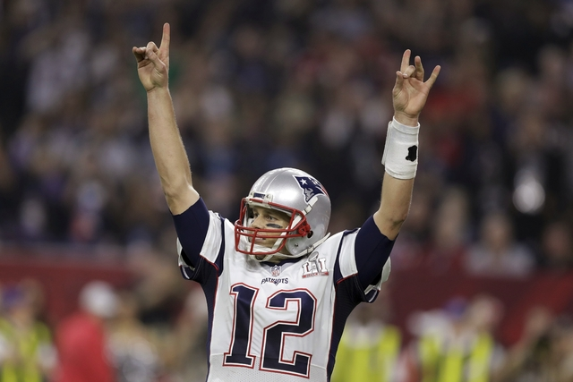 New England Patriots' Tom Brady raises his arms after scoring a touchdown during overtime of the NFL Super Bowl 51 football game against the Atlanta Falcons, Sunday, Feb. 5, 2017, in Houston. The  ...