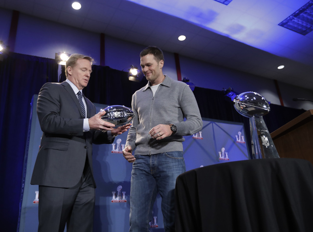 NFL commissioner Roger Goodell hands New England Patriots quarterback Tom Brady his MVP trophy during a news conference after the NFL Super Bowl 51 football game Monday, Feb. 6, 2017, in Houston.  ...