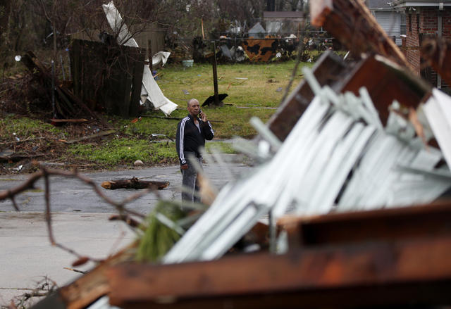 A man looks at a destroyed home after a tornado tore through the eastern part of New Orleans, Tuesday, Feb. 7, 2017. The National Weather Service says at least three confirmed tornadoes have touch ...