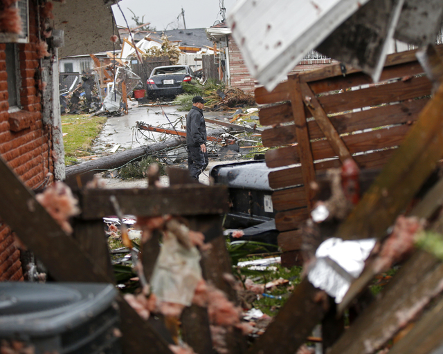A man walks down the street past destroyed homes after a tornado tore through the  eastern part of New Orleans, Tuesday, Feb. 7, 2017. (Gerald Herbert/AP)