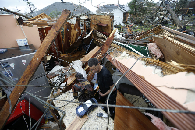 Gregory Rugon looks for his glasses at the spot where he took cover in his home after a tornado hit his Warren Drive home, in the New Orleans East section of New Orleans, Tuesday, Feb. 7, 2017. (G ...