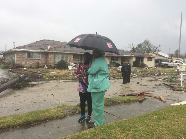 Linda Pierre, left, and April Williams look around the east New Orleans neighborhood after a tornado touchdown, Tuesday, Feb. 7, 2017. (Gerald Herbert/AP)