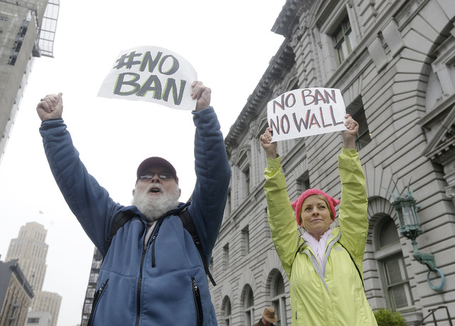 David Pearce, left, and his daughter Crissy Pearce hold signs outside of the 9th U.S. Circuit Court of Appeals in San Francisco, Tuesday, Feb. 7, 2017. President Donald Trump's travel ban faced it ...