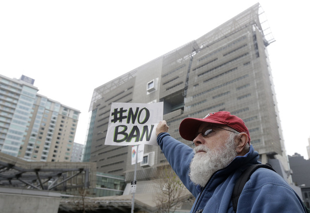 David Pearce holds a sign outside of the 9th U.S. Circuit Court of Appeals in San Francisco, Tuesday, Feb. 7, 2017. President Donald Trump's travel ban faced its biggest legal test yet Tuesday as  ...