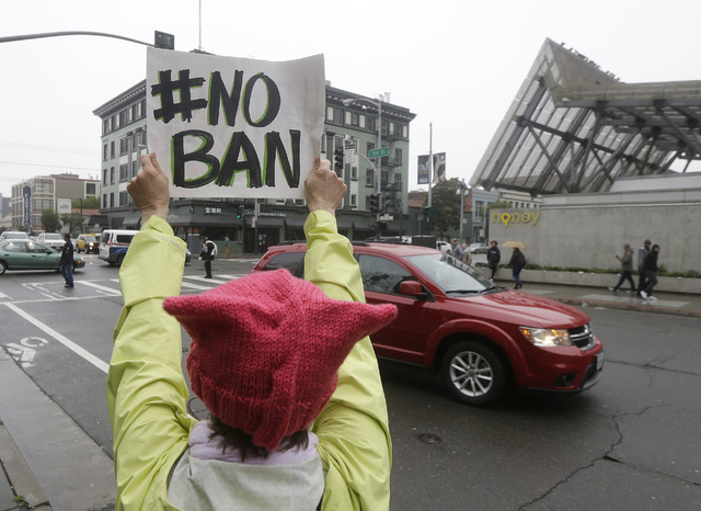 Crissy Pearce holds up a sign outside of the 9th U.S. Circuit Court of Appeals in San Francisco, Tuesday, Feb. 7, 2017. President Donald Trump's travel ban faced its biggest legal test yet Tuesday ...