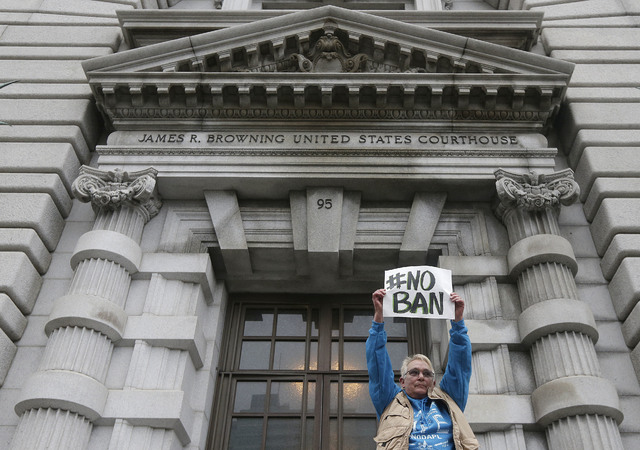 Karen Shore holds up a sign outside of the 9th U.S. Circuit Court of Appeals in San Francisco, Tuesday, Feb. 7, 2017. A panel of appeals court judges reviewing President Donald Trump's travel ban  ...