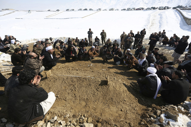 Villagers pray by the grave of a victim of a suicide attack on the Supreme Court in Kabul, Afghanistan, Wednesday, Feb. 8, 2017. A suicide bomber on Tuesday targeted the Supreme Court building in  ...