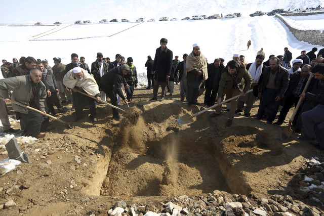 Men bury a victim of a suicide attack on the Supreme Court in Kabul, Afghanistan, Wednesday, Feb. 8, 2017. A suicide bomber on Tuesday targeted the Supreme Court building in the Afghan capital, Ka ...
