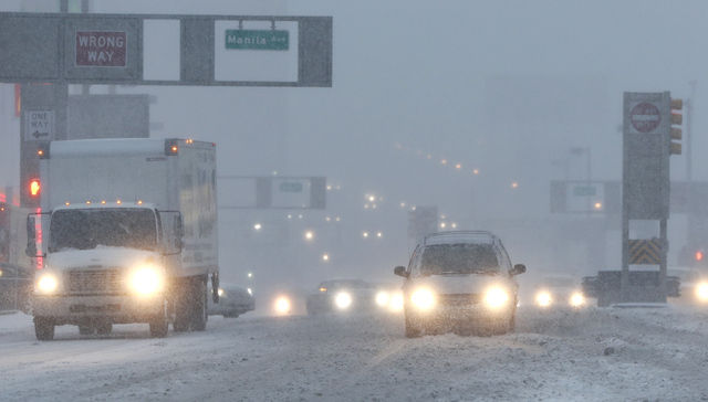 Vehicles drive drive through snow as they approach the Holland Tunnel, Thursday, Feb. 9, 2017, in Jersey City, N.J. A powerful, fast-moving storm swept through the northeastern U.S. early Thursday ...