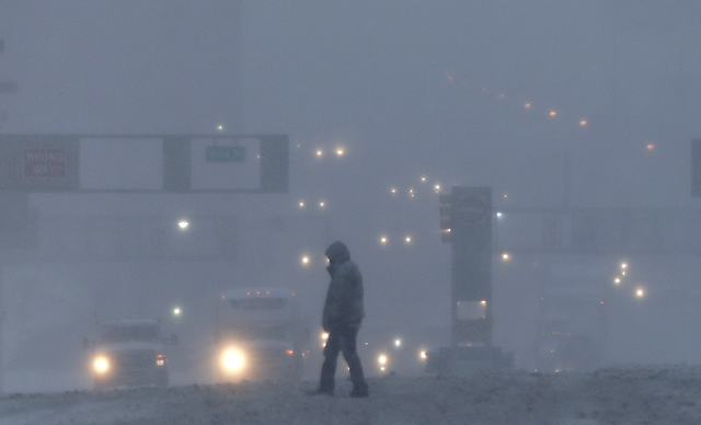 A pedestrian crosses as snow-covered intersection as snow falls, Thursday, Feb. 9, 2017, in Jersey City, N.J. A powerful, fast-moving storm swept through the northeastern U.S. early Thursday, maki ...